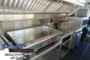 photo of food truck interior showing a grill and exhaust hood