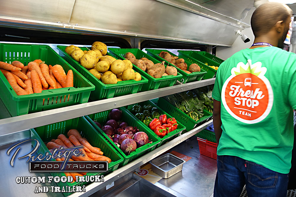 shelves with trays full of vegetables and a Fresh Stop food truck employee