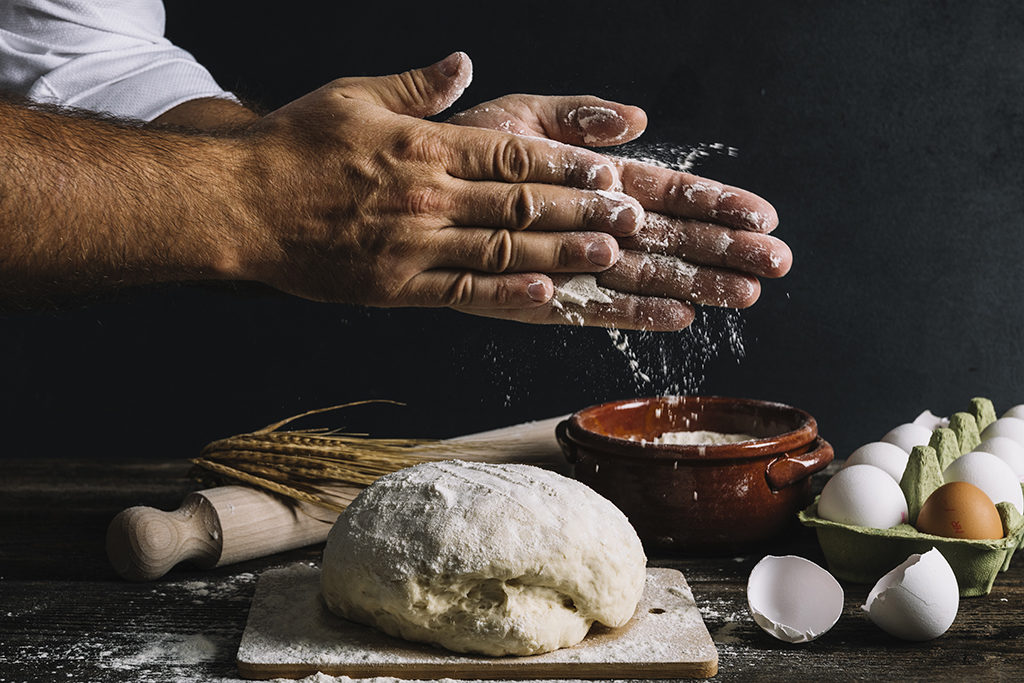 close up of chef hands rubbing flour between them above a ball of dough with various food ingredients in the background