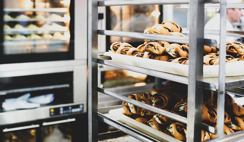 photo of a bakery interior with cinnamon rolls cooling on a baking rack in the foreground and ovens filled with baking goods in the background