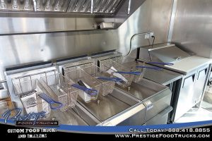 food truck interior with fryer baskets and sandwich prep table