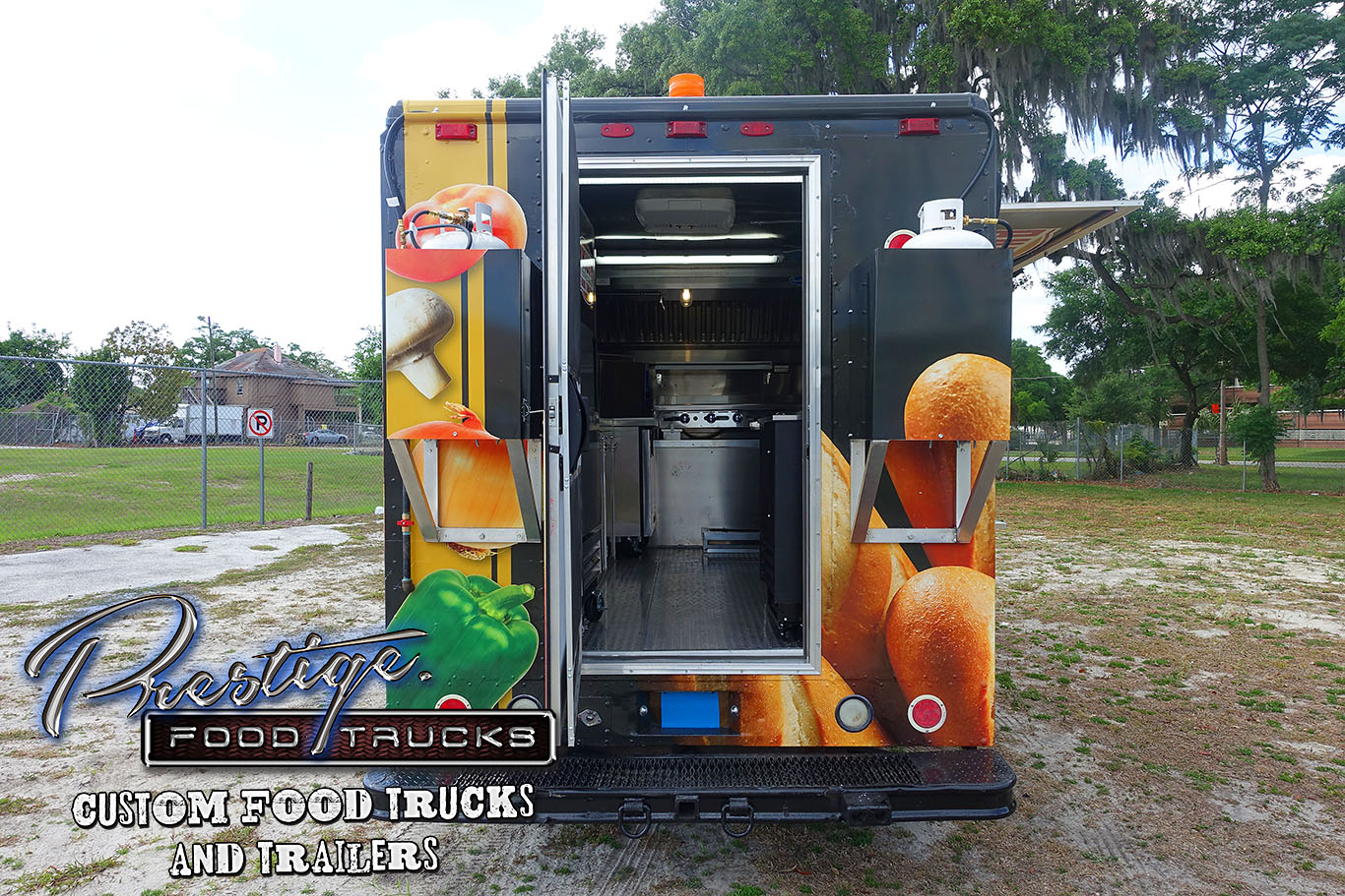 rear view of black food truck with rear door open to reveal inside kitchen