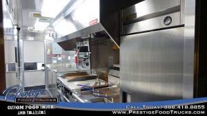 food truck interior with fryers, grill and exhaust hood