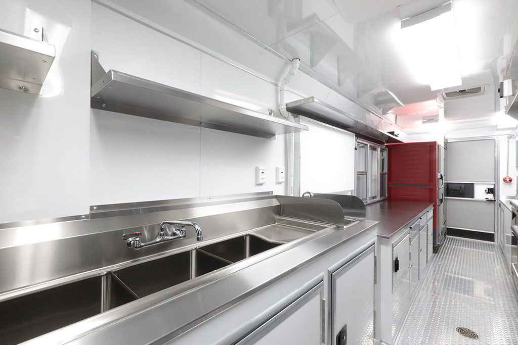 angled photo of one side of a food truck interior with sink, countertop, fridge, and serving window