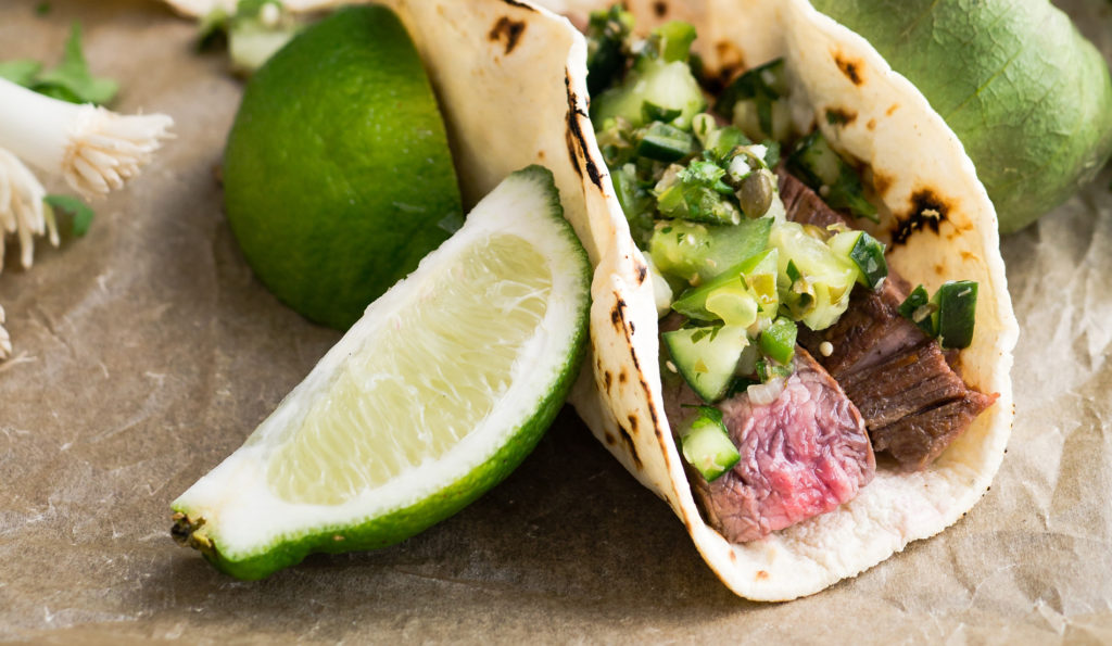 close-up photo of a steak taco with green salsa and limes on the side