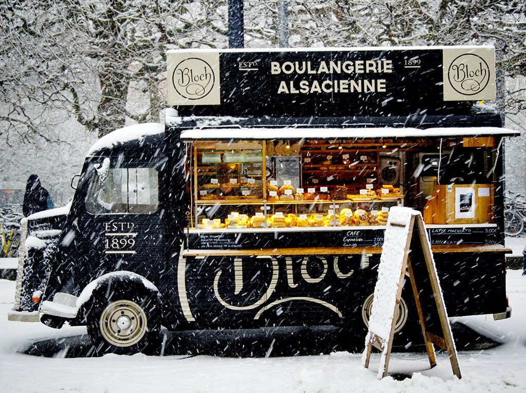 black vintage food truck selling baked goods in a snowy winter scene