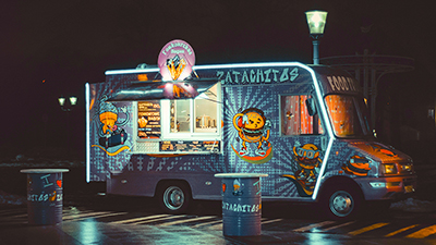 Photo of a blue burger food truck with neon lights parked under a streetlamp in a parking lot