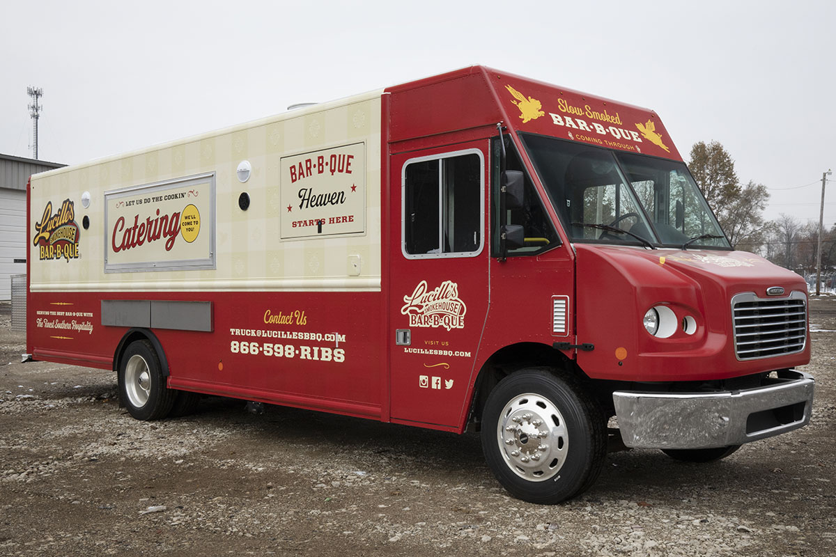 front 3/4 angle photo of a red and cream colored food truck with serving windows closed