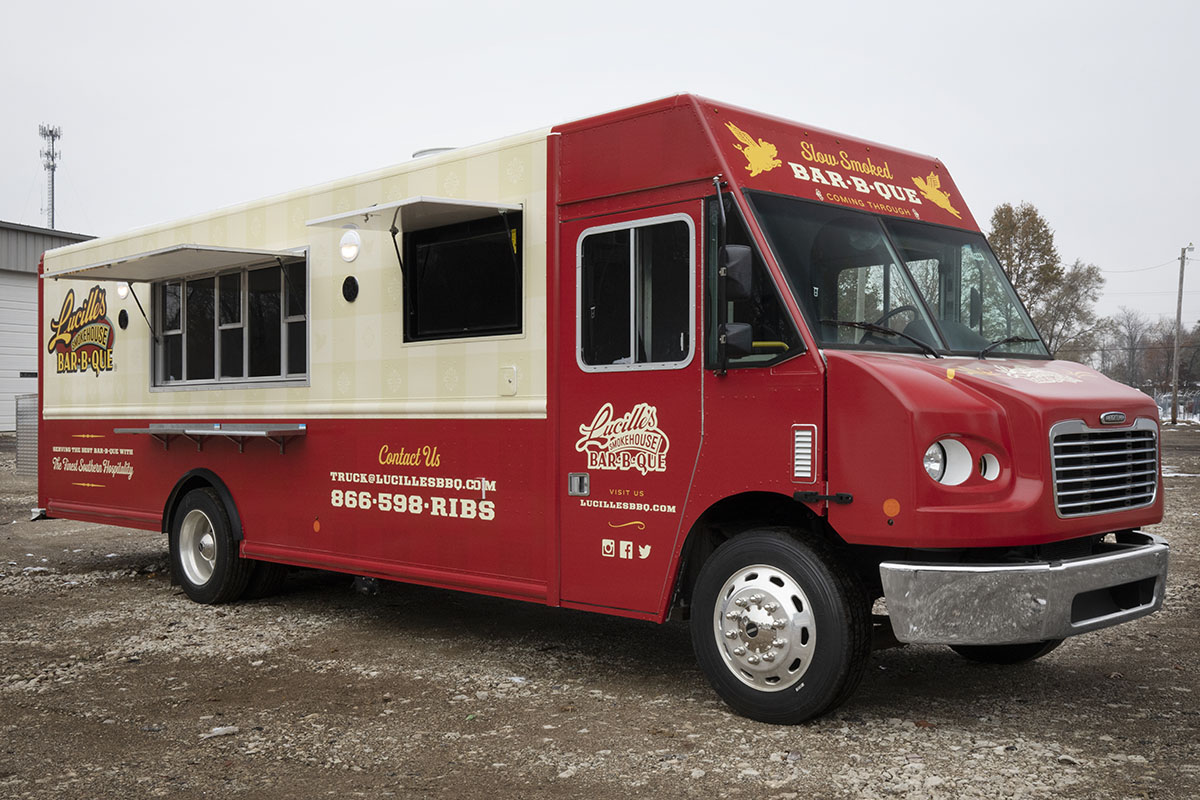 front 3/4 angle photo of a red and cream colored food truck with serving windows open