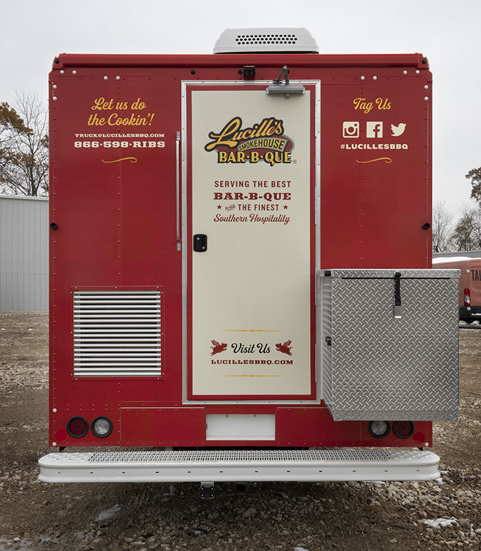 rear view photo of a red and cream colored food truck with back door closed