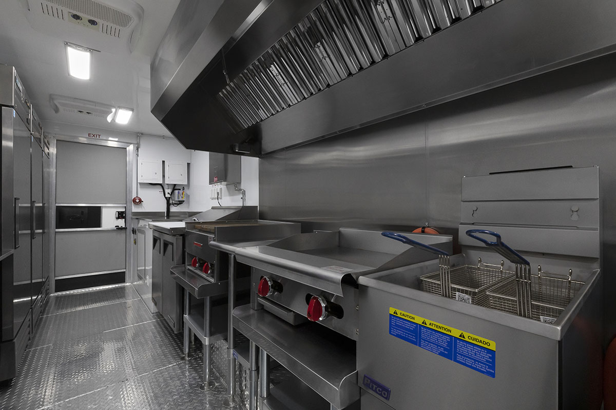 food truck interior kitchen photo showing deep fryer, griddle, sandwich prep table and exhaust hood