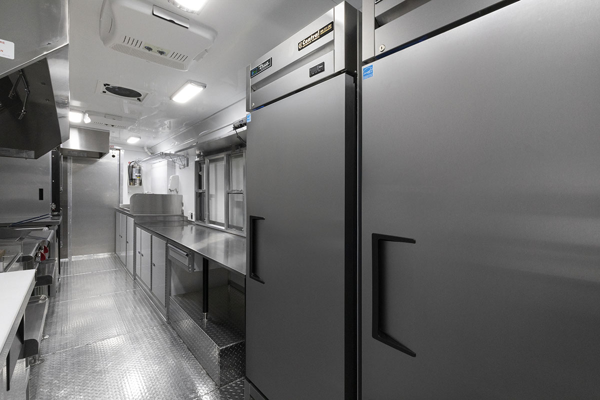 food truck interior kitchen photo showing fridges, counter, and sinks with driver door open