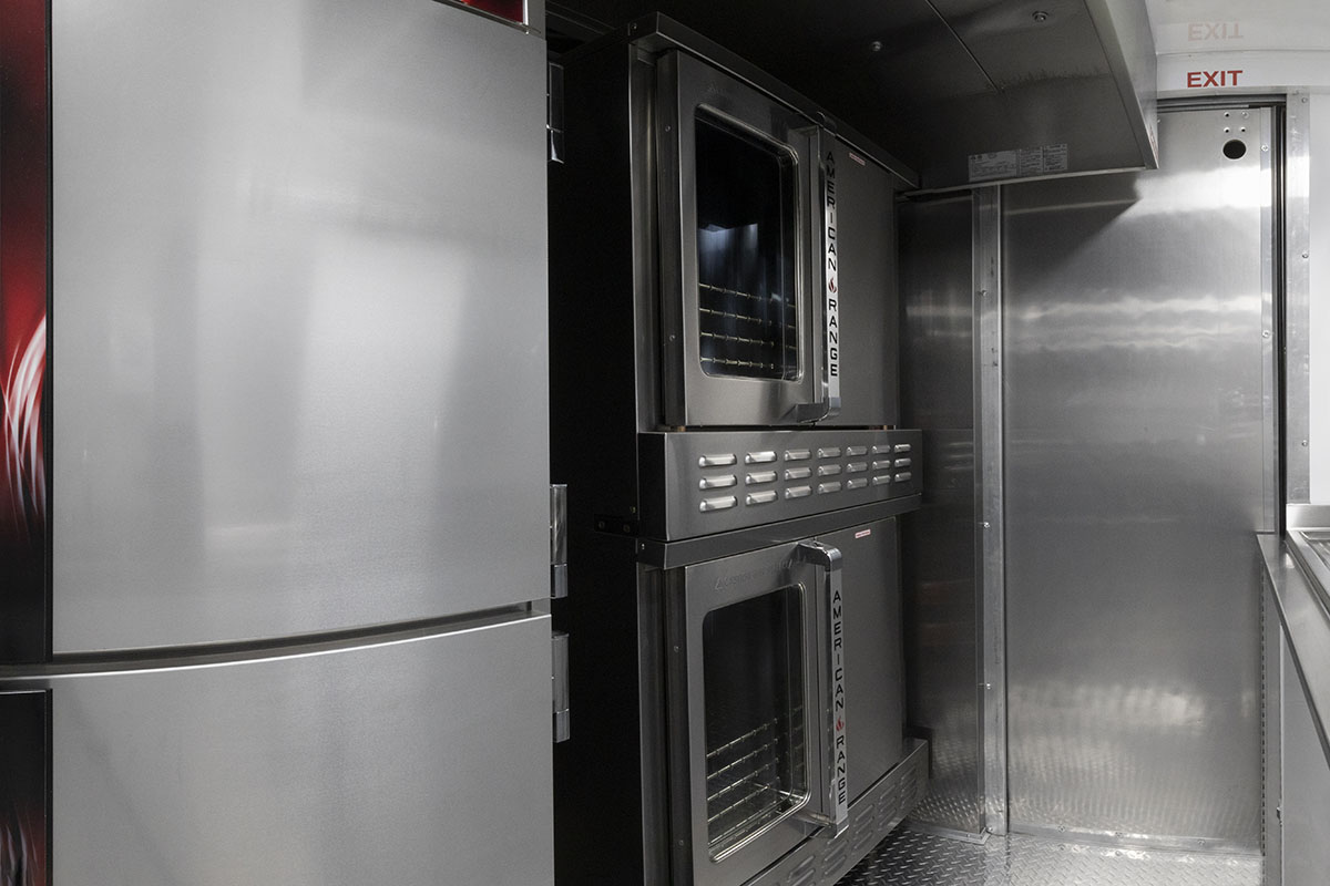food truck interior kitchen photo showing proofing cabinet, ovens and closed driver door partition