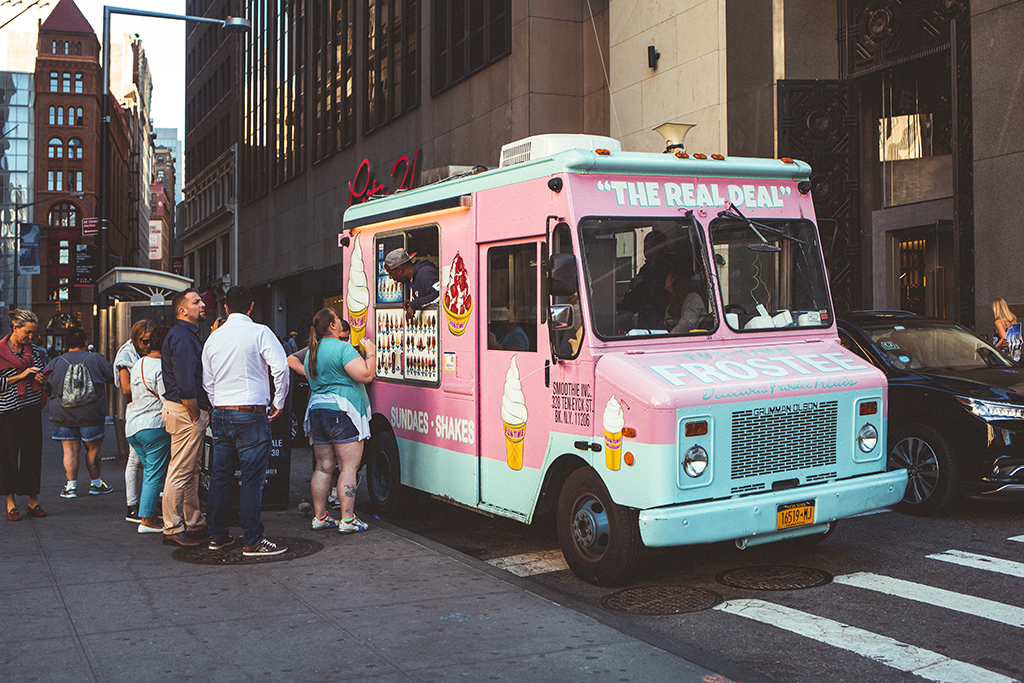 photo of a small pink food truck serving ice cream parked on a city street with a line of customers waiting