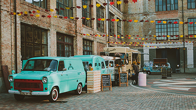photo of several food trucks parked in a courtyard between brick buildings