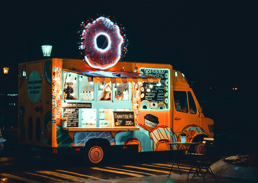 photo of an orange and blue food truck at night time with a neon donut sign