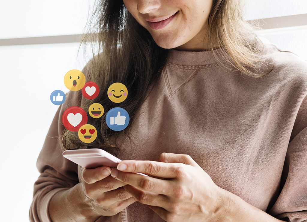 photo of a smiling young white woman looking down at her phone with overlay of animated floating Facebook likes, hearts and emoji faces emanating from the phone screen