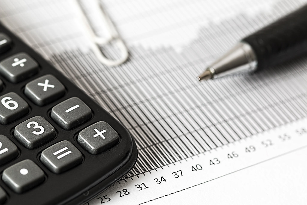 close up photo of a pen, calculator and financial charts