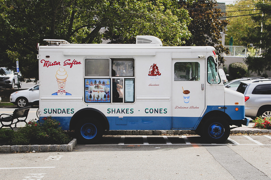 photo of a white and blue ice cream truck parked in a parking lot on a sunny day