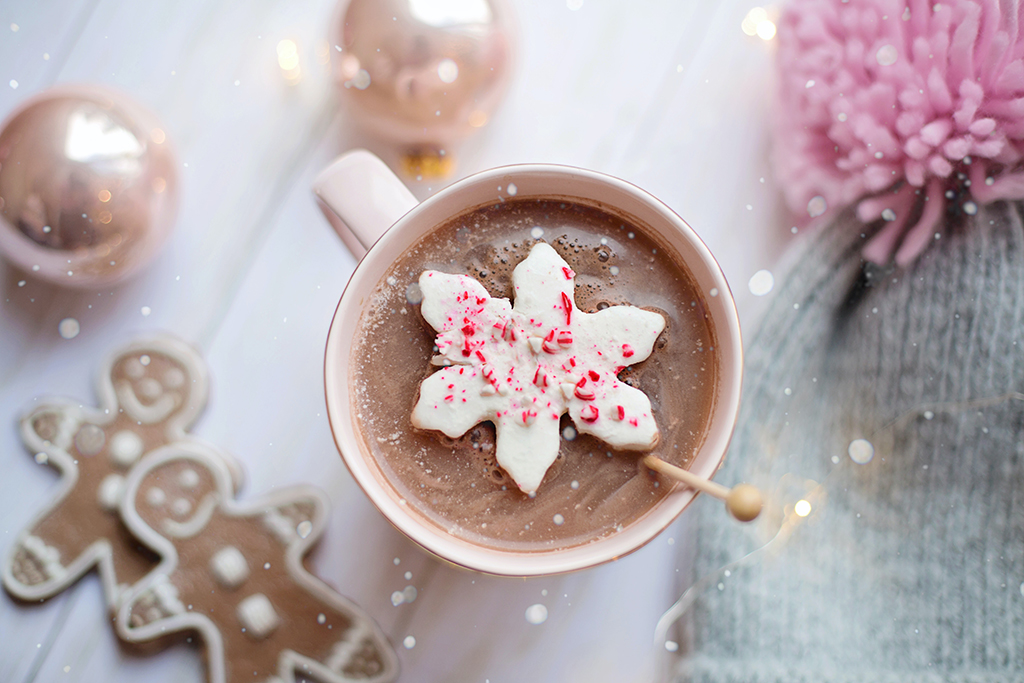 festive holiday photo of hot chocolate on a table with gingerbread, ornaments, and a winter hat