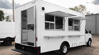 small white food truck parked with serving windows open